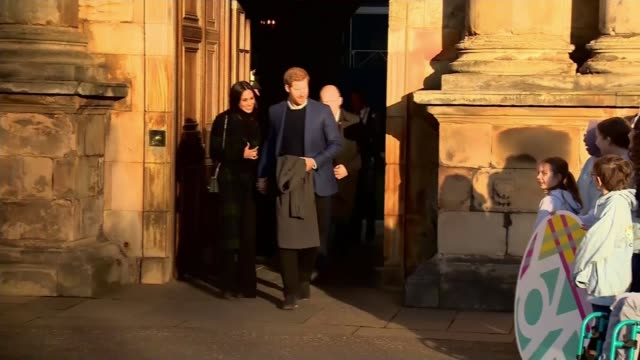Prince Harry and Meghan Markle on visit to Scotland EXT Markle and Prince Harry towards from Holyrood House building to applause Royal standard flag...