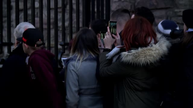 Prince Harry and Meghan Markle on visit to Scotland Reporter to camera as Royal car leaves in background Fans taking photographs through gates INT...