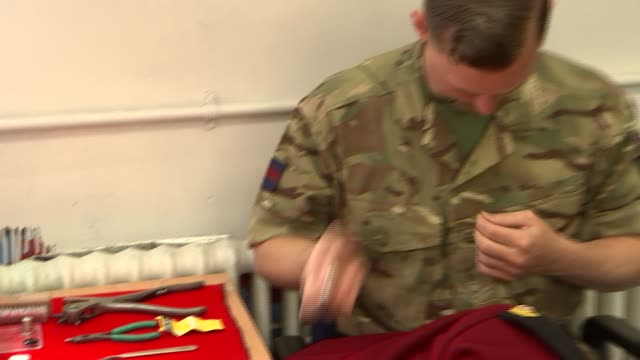 Household Cavalry preparations at Hype Park Barracks INT GVs soldiers in uniform sewing room / various of uniforms and detail / soldiers sewing...