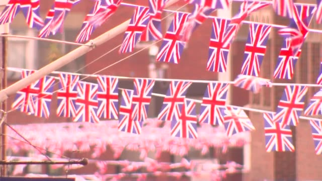 prince harry and meghan markle wedding: preparations in windsor; tourists wearing union jack clothing and flags / union jack bunting across street /... - union jack stock videos & royalty-free footage