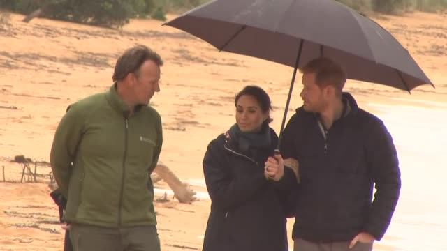vídeos de stock e filmes b-roll de prince harry and meghan, the duke and duchess of sussex, walking on beach in rain during visit to abel tasman national park, on day two of their... - realeza