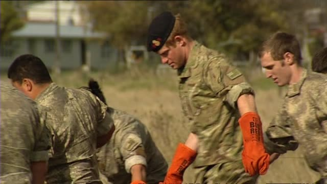 Prince Harry assisting soldiers in removing food from hangi pit at Linton Army Camp