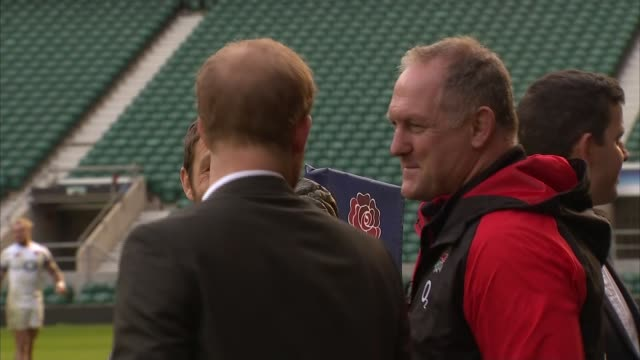 Prince Harry attends open training session at Twickenham ***MUSIC Harry getting up from stands / chatting to woman with baby / Various of rugby...
