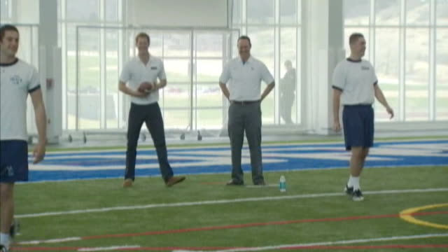 Prince Harry continues his visit to USA Harry training with American football team throwing and receiving passes Harry presented with football shirt...