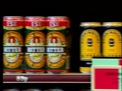 police involvement lib cans of 'flowers bitter' on display on shelf in off licence pan other cans of bitter gv bottles of beer on shelf crates of... - lager stock videos & royalty-free footage