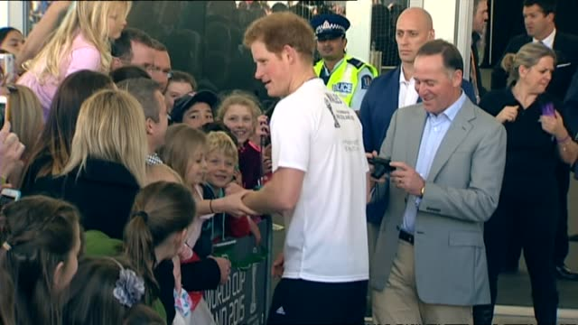 Prince Harry greeting wellwishers and posing with fans while Prime Minister John Key takes photograph following 2015 FIFA U20 World Cup promotional...
