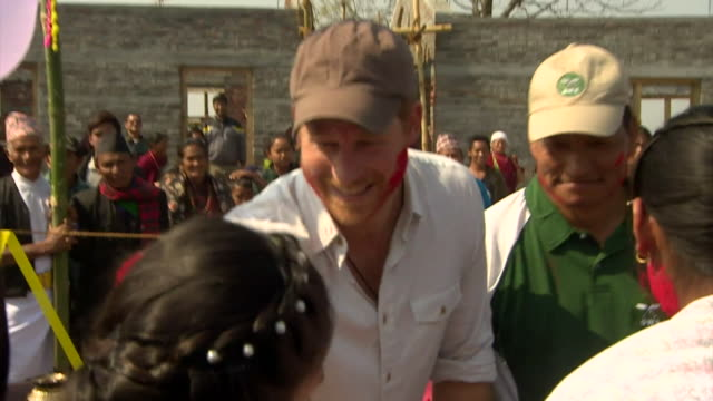 prince harry has his face smeared with red dye at a hindu festival of colour in nepal - nepal stock-videos und b-roll-filmmaterial