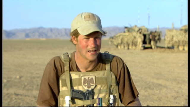 prince harry is serving in afghanistan; afghanistan: helmand province: ext prince harry in the field with other british soldiers of the household... - 連隊点の映像素材/bロール