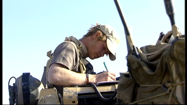 On patrol with MOG tank unit February 2008 AFGHANISTAN Helmand Province EXT Prince Harry sitting on top of tank speaking on radio calling in 'Show of...