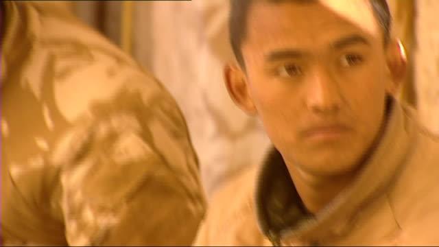 stockvideo's en b-roll-footage met prince harry is serving in afghanistan: prince harry at fob delhi; ext smoke from chimneys / gurkha soldier looking at water being heated in drums... - artikel