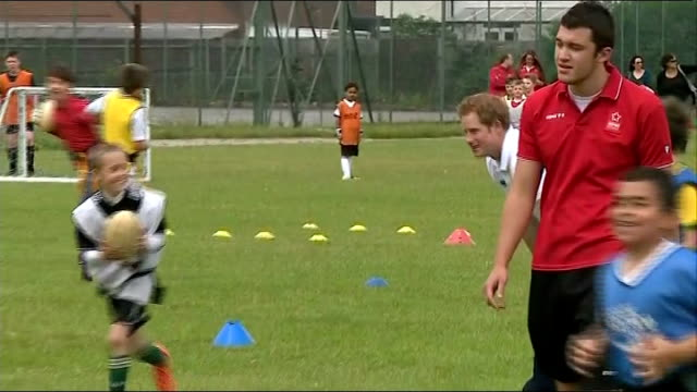 Prince Harry joins children for football and rugby training in Ipswich Prince Harry putting on waistband to join in game of tag rugby / various of...