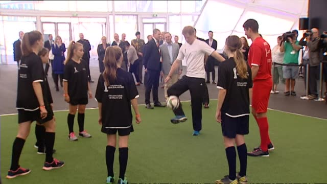 Prince Harry kicking soccer ball around with group of girls observed by veteran Royal photographer Arthur Edwards prior to 2015 FIFA U20 World Cup...