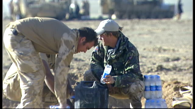 vídeos de stock, filmes e b-roll de prince harry on patrol in afghan desert tank patrol preparing for departure including filling container up from bottles of mineral water as harry... - 2008