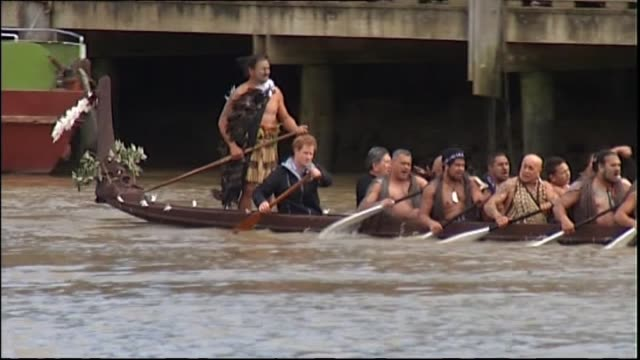 Prince Harry paddling in waka with local Māori on Whanganui River and waving to wellwishers