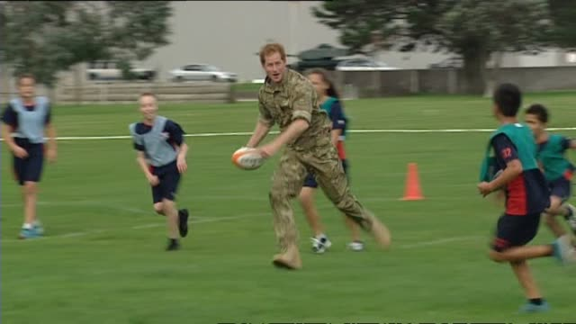 Prince Harry playing game of touch rugby with children from Linton Army Camp School
