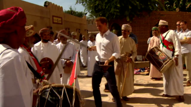 prince harry sword fights during visit oman nizwa nizwa fort ext man beating frum and signing to welcome prince harry prince harry holding sword and... - oman stock videos & royalty-free footage
