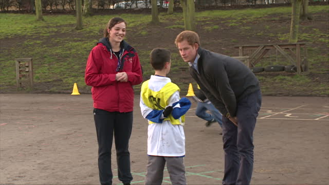 nottingham prince harry talking to teacher and young boy during football lesson in playground - contea di nottingham video stock e b–roll