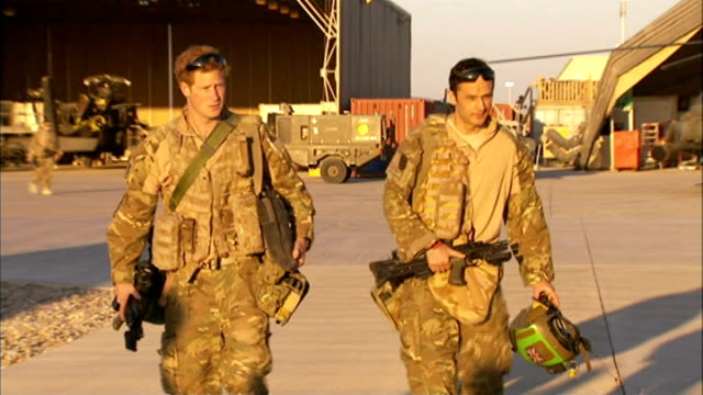 Prince Harry to leave British Army LIB Shot in November 2012 AFGHANISTAN Helmand Province Prince Harry and colleague walking along Apache helicopter...