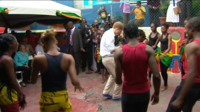 prince harry tour to mark diamond jubilee of queen; jamaica: kingston: ext prince harry led up to dance to bob marley music by woman from the rise... - ボブ・マーリー点の映像素材/bロール