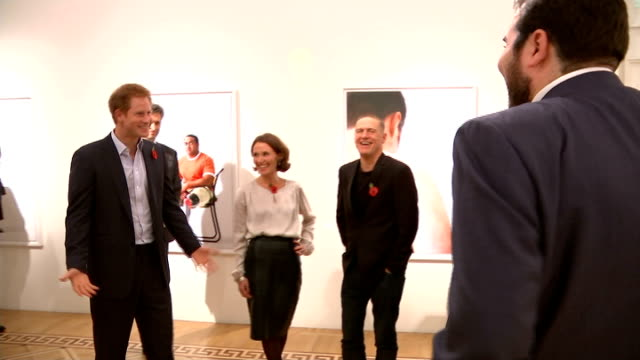 vidéos et rushes de prince harry tours wounded exhibition veterans and harry discussing where money from book will go sot / close shot prince harry smiling / close shot... - bryan adams