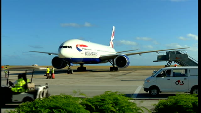 arrival at airport barbados bridgetown grantley adams airport ext british airways plane taxiing to a halt at airport airport workers putting chocks... - bremskeil stock-videos und b-roll-filmmaterial