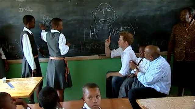 stockvideo's en b-roll-footage met prince harry visits children supported by his charity sentebale; lesotho: ext prince harry, prince seeiso and group of children dancing and holding... - home economics