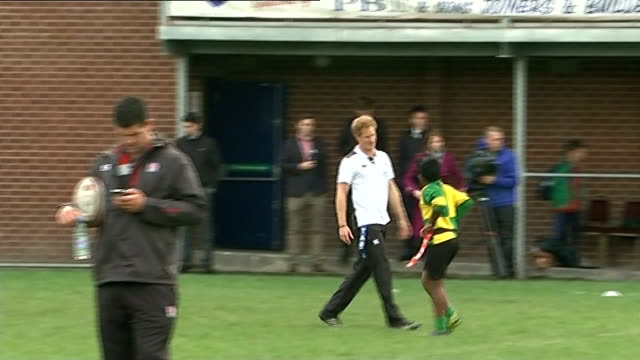 Prince Harry visits Eccles RFC More shots of Harry and children playing rugby / Harry children and other rugby players posing for group photocall