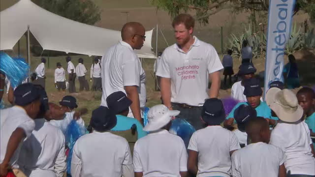 Prince Harry visits Mamohato Children's Centre with Sentebale charity Shows exterior shots Prince Harry Prince Seeiso surrounded by children on...
