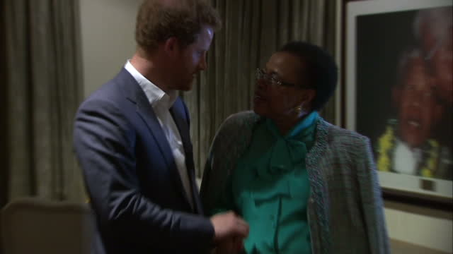 prince harry visits the nelson mandela centre shows interior shots prince harry walking into room with graca machel widow talking together on... - waisenhaus stock-videos und b-roll-filmmaterial