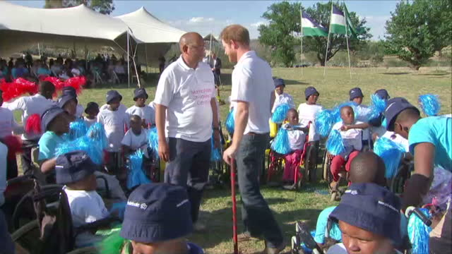 prince harry was greeted with a hug from an 'old friend' when he visited a children's centre in lesotho today mutsu potsane who lost both his parents... - waisenhaus stock-videos und b-roll-filmmaterial