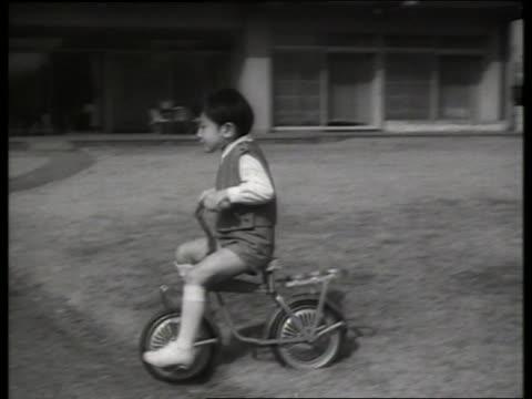 prince hiro of japan riding bicycle / 1960's / sound - solo bambini maschi video stock e b–roll