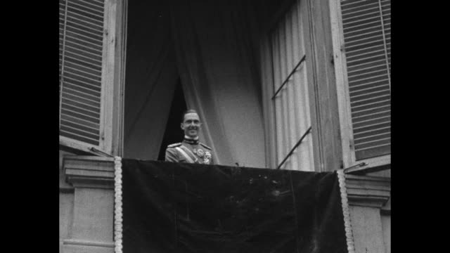 MS Prince Humbert stands on balcony of his new private residence / MS huge crowd cheers below waves hats and handkerchiefs