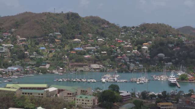 prince of wales and duchess of cornwall visit grenada grenada st george's gvs over bay / flags flying outside parliament building and mps gathered - st. george's grenada stock videos and b-roll footage