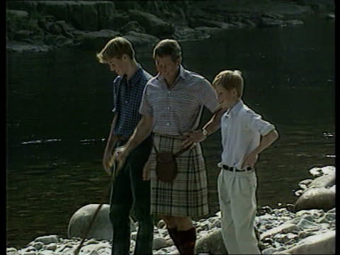 vídeos de stock, filmes e b-roll de prince of wales biography row lib balmoral ext charles with sons prince william and prince henry next river prince william with dog beside river - biografia