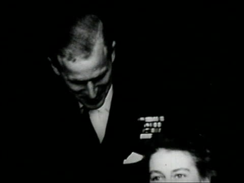 prince philip and princess elizabeth pose for portraits during their engagement announcement / they exit building and the prince holds her coat so... - 1947年点の映像素材/bロール