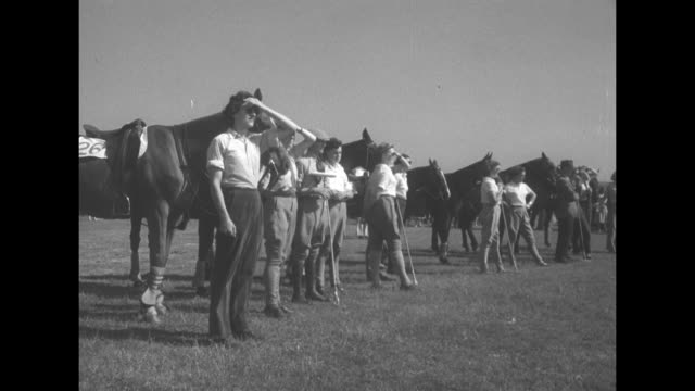 MS Prince Philip climbs on polo horse number 24 / QS people sitting on ground watch / MS polo match / MS men and women in polo trousers stand with...
