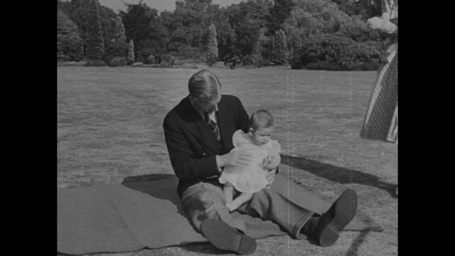 Prince Philip Duke of Edinburgh lifts baby Prince Charles out of carriage holds him in air as wife Princess Elizabeth looks on then sits on blanket...