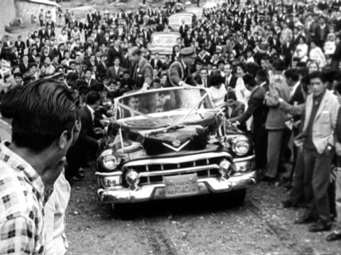 prince philip jokes with the locals of la paz as his car moves up a steep slope. 1962. - schieben stock-videos und b-roll-filmmaterial