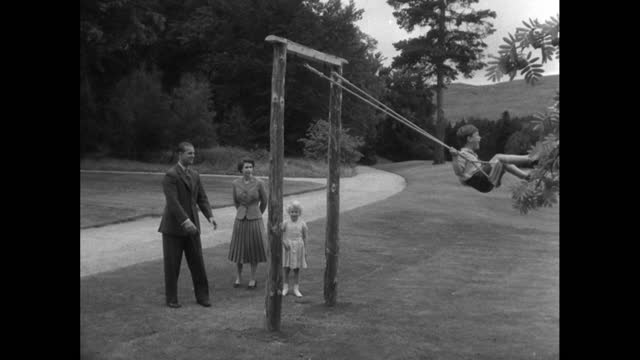 prince philip pushes prince charles on a swing as queen elizabeth ii and princess anne watch during a family holiday at balmoral; 1955. - concepts & topics stock videos & royalty-free footage
