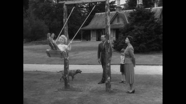 prince philip pushes princess anne on a swing as queen elizabeth ii and prince charles watch during a family holiday at balmoral; 1955. - concepts & topics stock videos & royalty-free footage