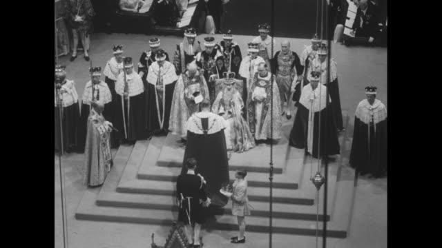 WS Prince Philip the Duke of Edinburgh kneels before the queen the first to pay fealty and homage / they kiss / the queen sitting on the Chair of...