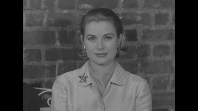 ws prince rainier and grace kelly sit on bench in front of brick wall for press conferencephoto op / vs both of them together and individually / her... - fiancé stock videos and b-roll footage