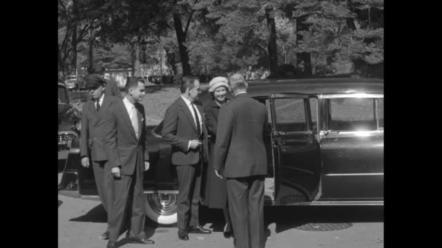 prince rainier assists grace kelly out of car greeted by white house staff / press photographers / they pose before entering / press follows them to... - fürst rainier iii. von monaco stock-videos und b-roll-filmmaterial