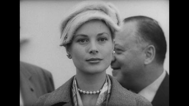 Prince Rainier Grace Kelly at microphones on deck of steamship Prince waves she looks around / WS SS United States at dock / Rainier Kelly step up to...