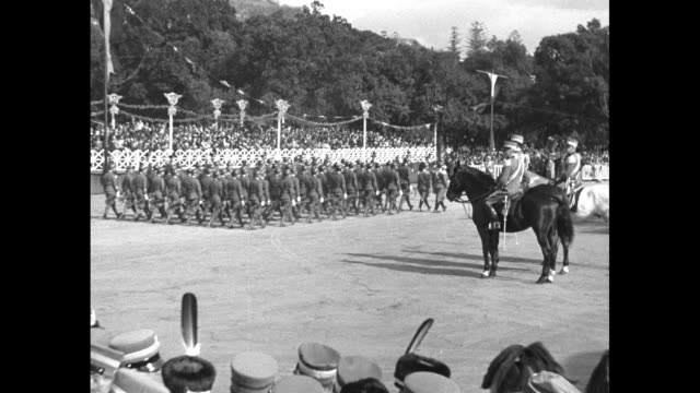 prince umberto sits on horse reviewing the troops from the 25th brigade as they march by, the town rises on mountainside beyond the parade ground,... - war stock-videos und b-roll-filmmaterial