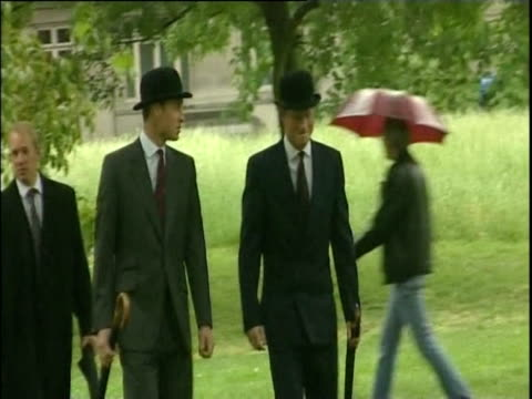 Prince William and Prince Harry walking together in rain wearing bowler hats and carrying umbrellas London May 2007