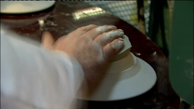 aynsley china produces line of commemorative crockery various of commemorative mugs and plates coming out of kiln / general vites of potter shaping... - kiln stock videos and b-roll footage