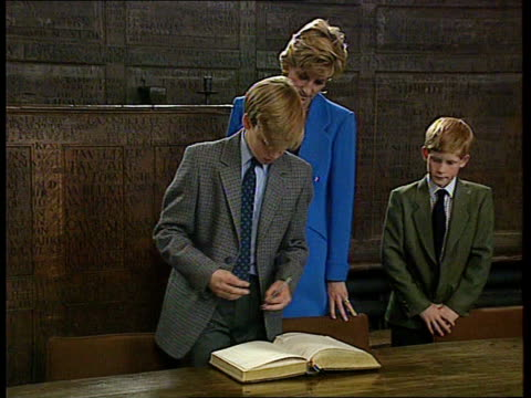 prince william first day at eton int ms william sits to sign book as diana and harry behind cms william signing - 1日目点の映像素材/bロール
