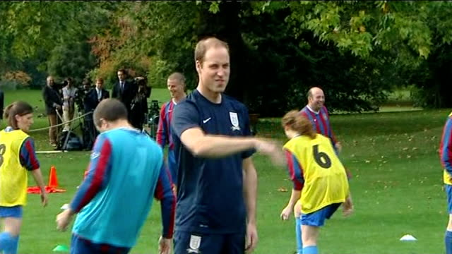 prince william organises football match at buckingham palace ext gvs prince william running and kicking ball with others in training session william... - フットマン点の映像素材/bロール