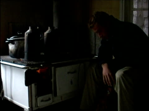 Prince William sits by stove complaining about how early it is in morning during Raleigh International expedition Patagonia 11 Dec 00